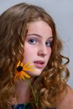 Girl with Flower. Pretty young girl posing with echinacea flower next to face Stock Photography
