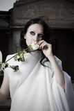 Girl with flower. Pretty gothic girl in white clothes with flower Royalty Free Stock Photos