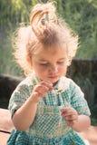 Girl with flower. Little blond girl holding daisy flower Stock Photo