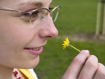Girl with flower. Young lonly girls face and beauty small yellow flowers in her hand Stock Photography