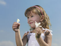 Girl with flower. On blue sky Royalty Free Stock Images
