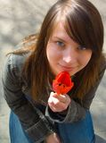 The girl and a flower. The girl with a flower on a background of asphalt royalty free stock images