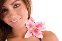 Girl and flower. A studio closeup of a pretty teenage girl posing with a pinkish lily flower on her shoulder Stock Photos