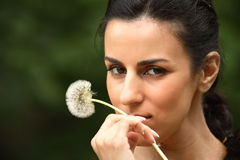Girl and flower. The girl is holding in the mouth flower Stock Image