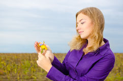 Girl with flower. Blondie girl watching on the flower Stock Images