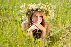 Girl  in flower chaplet. Long-haired  girl  in flower chaplet in grass Stock Image