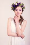 Girl with flower crown posing in studio. White background, portrait Stock Photos