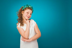 Girl with flower decorations. White dress. Turquoise background. Stock Images