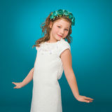 Girl with flower decorations. White dress. Turquoise background. Royalty Free Stock Image