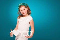 Girl with flower decorations. White dress. Turquoise background. Royalty Free Stock Photo