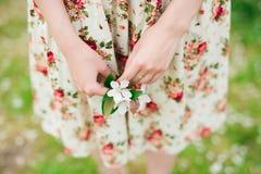 Girl in flower dress holding sakura cherry blossom in hands Stock Photo