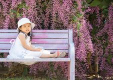Girl with flower. A female kid in a white dress sitting on a bench with beautiful purple flower background Stock Photo