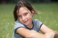 Girl in flower field. Portrait of a girl daydreamming in flower field royalty free stock photo