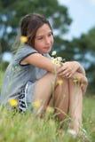 Girl in a flower field. Portrait of a girl daydreamming in flower field stock image