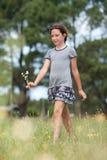 Girl in a flower field. Girl walking in a flower field royalty free stock photography