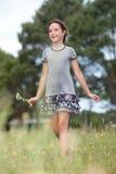 Girl in a flower field. Girl walking in a flower field royalty free stock photo