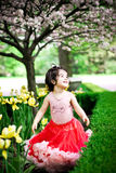 Girl in flower garden. Cute girl in a flower garden wearing a cute pettiskirt Royalty Free Stock Photography