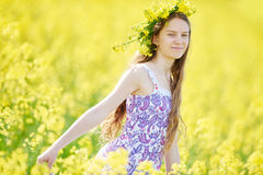 Girl with flower garland at yellow rape seed meadow Royalty Free Stock Image