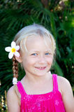 Girl with flower in hair. Outdoor portrait of a cute little young Caucasian white girl with happy smiling expression in her face and beautiful white and yellow royalty free stock photos