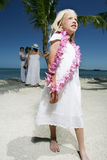 Girl with flower lei. A view of a pretty young girl in a white dress, walking on a sandy beach, wearing a purple flower lei Royalty Free Stock Images