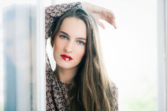 Girl with flower in mouth Stock Images