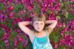 Girl on flower petals. Little girl laying on flower petals with heads behind her head Royalty Free Stock Image