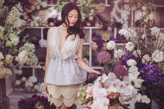 Asian woman in flower shop. Girl in flower store. Woman standing against floral bokeh background in floral shop. Joyful asian female. Playful fashion model royalty free stock image