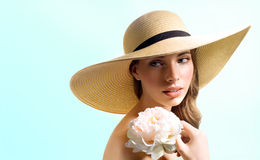 Girl with flower in straw hat. Studio portrait beautiful young woman in summer straw hat with fields, holding a flower Archidom on a blue background Royalty Free Stock Photos