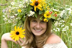 Girl with flower wreath. In the meadow Stock Image