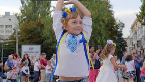 Girl in flower wreath at festivity, kid with bright ribbon in hands dances in square, child in national costume stock video