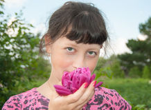 Girl with flower. A young, smiling girl with a pink flower Stock Photo