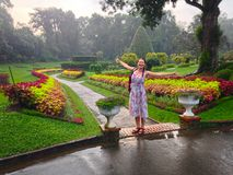 Girl, flowerbeds with flowers in Royal Botanical Garden. In Kandy Sri Lanka stock photos
