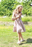 Girl in flowered dress carrying ground Stock Photo