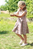 Girl in flowered dress carrying ground Royalty Free Stock Photo