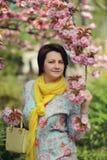 Girl in the flowered garden Stock Image