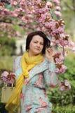 Girl in the flowered garden Stock Photos