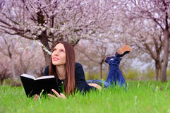 The girl in the flowered garden lies on the grass and reading a Royalty Free Stock Image