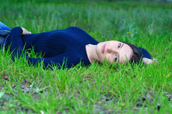The girl in the flowered garden lying on the grass Stock Photography