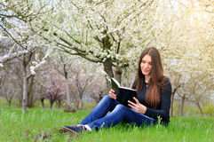 The girl in the flowered garden sit on the grass and reading a b Stock Photo