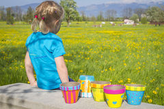 Girl on flowering field with colorful painted garden pots Royalty Free Stock Images