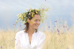 Girl in a flowering field. In a lush field girl with a wreath of flowers on her head royalty free stock images