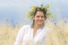 Girl in a flowering field. In a lush field girl with a wreath of flowers on her head royalty free stock photo