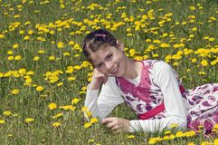 Girl in the flowering meadow smiling Stock Photography