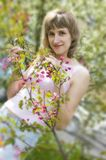 Girl with a flowering tree Stock Image