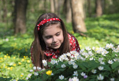 Girl in flowers. Little girl sitting in a flowers in the woods Royalty Free Stock Image