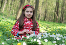 Girl in flowers. Little girl sitting in a flowers in the woods Royalty Free Stock Photos