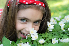 Girl in flowers. Little girl sitting in a flowers in the woods Stock Image