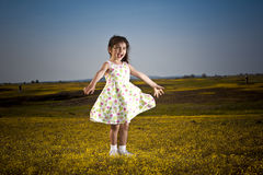 Girl in the flowers. Little girl twirling in the flowers in a meadow with a blue sky Stock Images