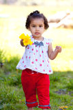 Girl With Flowers. A very young african american (black) girl holds some flowers while wearing a white and red outfit stock image
