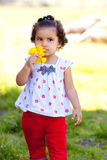 Girl With Flowers. A very young african american (black) girl holds some flowers while wearing a white and red outfit stock photos